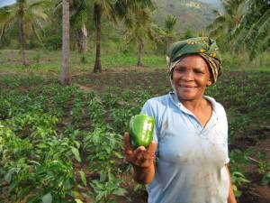 Mama Tatu proudly displays the fruit of her first ever green pepper harvest.