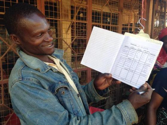 Hamisi shows off his new sales record book that tracks the details of each and every group sale from the Bungu Project.